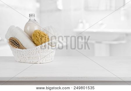White Basket With Spa Products On Wooden Table Inside Bathroom