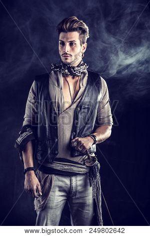 Good Looking Young Man Dressed In Pirate Fashion Outfit On Black Background With Smoke. Captured In