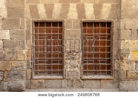 Two Similar Adjacent Wooden Windows With Iron Grid Over Decorated Stone Bricks Wall, Medieval Cairo,
