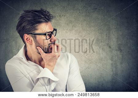 Adult Bearded Man Having Panic And Phobia Looking Away While Biting Nails In Anxiety On Gray Backgro