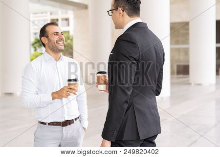 Portrait Of Happy Male Colleagues Drinking Coffee And Laughing In Office Corridor. Mid Adult Caucasi