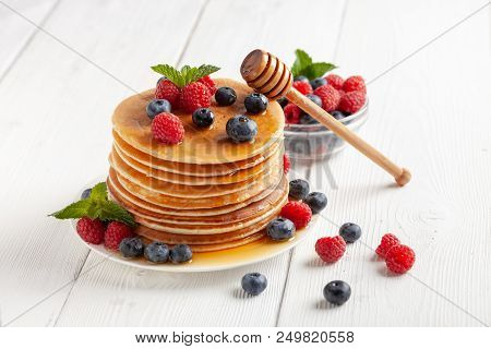 American Blueberry And Raspberry Pancakes On White Wooden Table