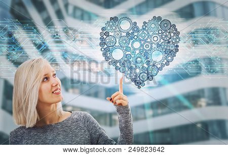 Portrait Of Smiling Woman Pointing Finger Up Showing A Gear Heart Hologram. Future Technology Artifi