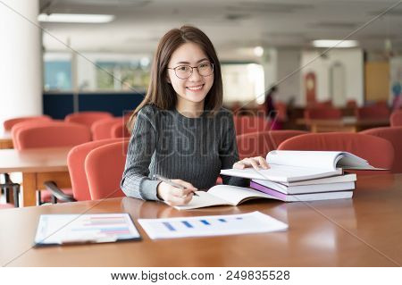 Female Student Taking Notes From A Book At Library, Young Asian Woman Sitting At Table Doing Assignm