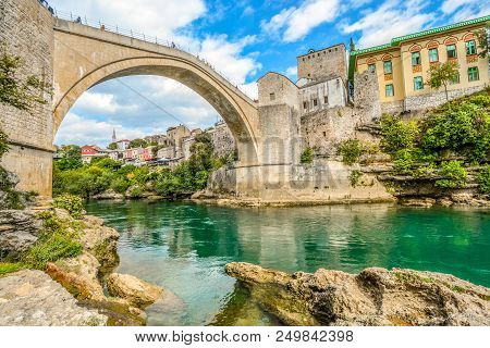 The Emerald Green Waters Of The River Neretva Flow Under The Mostar Bridge In The Ancient City Of Mo