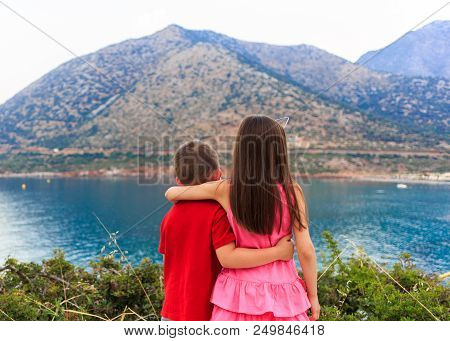 Girl And Boy Together Outdoors. Small Brother Embracing Older Sister Near The Sea.