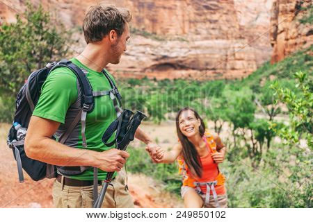 Man helping girlfriend climbing up rock during travel hike. Hikers hiking - Young guy hand holding for help. Challenge and team support concept.