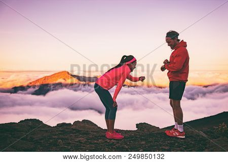 Runners tired exhausted during cardio effort using their wearable technology smartwatch checking heart rate monitor. Two athletes couple running together in outdoors mountains landscape. poster