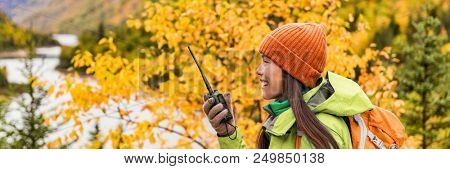 Autumn hiker girl talking on ham radio portable transceiver . Amateur radio operator woman holding handheld walkie-talking in outdoor nature landscape banner panorama crop. Active lifestyle. poster