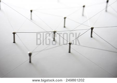 Connecting people and machines. Networking, internet infrastructure communication abstract. Entities of a network connected to each other. Web of thin silver wires on white background.