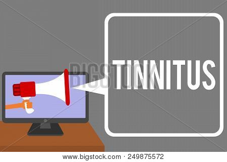 Conceptual hand writing showing Tinnitus. Business photo showcasing A ringing or music and similar sensation of sound in ears Man holding Megaphone computer screen talking speech bubble poster