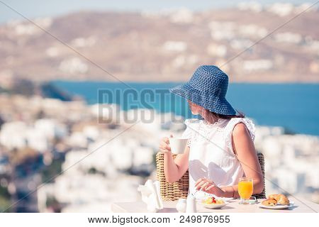 Beautiful Elegant Girl Having Breakfast At Outdoor Cafe With Amazing View On Mykonos Town. Woman Dri