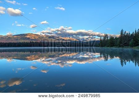 Morning Sun And Low Clouds Cover The Rocky Mountains At Annette Lake In Jasper National Park With Re