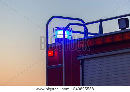 Flashing lights of red fire truck at dusk