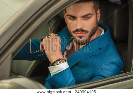 handsome man in blue suit driving his car looks on window while holding sunglasses