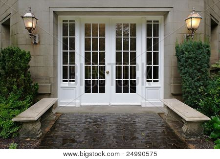 Elegant stone walkway bordered by stone benches leading to a double glass paned front door with two large front lanterns
