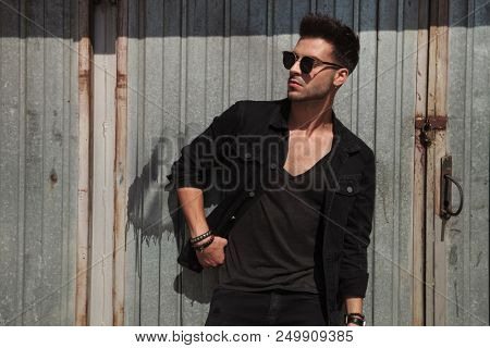 casual man standing on metal wall background looks to side while wearing black shirt and sunglasses, portrait picture