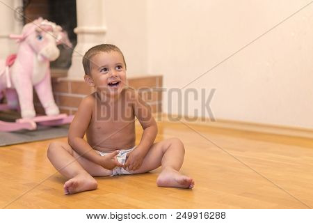 Baby Boy Laughing In The Playroom. Cute Baby Boy Laughing And Showing Baby Teeth With Toys On A Blur