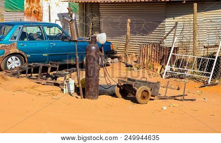 Johannesburg, South Africa, September 11, 2011, Small Informal Hawker Repairing Vehicle Exhausts On