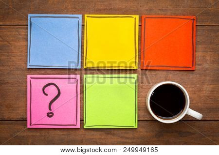 question mark and blank reminder notes - handwriting on colorful sticky notes with a cup of coffee