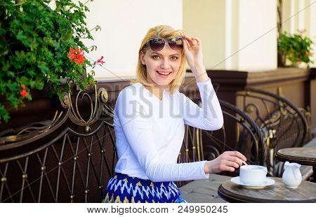 Woman happy cheerful face have drink cafe terrace outdoors. Girl drink tea with milk as aristocratic tradition. Traditional tea with milk. Mug of good tea with milk in morning gives me energy charge. poster