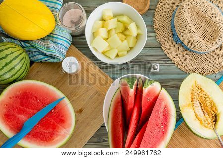 Summer Still Life Of A Picnic Table With Fresh Sliced Bright Yellow Canary Melon And Wedges Of Water