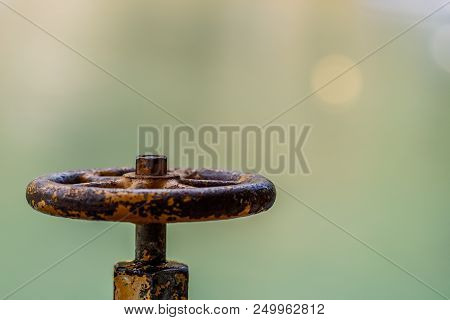 The Old Rusty Metal Valve On A Blurred Background.