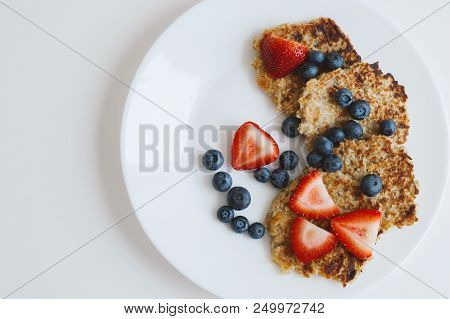 Brown Pancakes From Whole Grain Oats Served With Fresh Bluberry And Sliced Strawberry On White Backg
