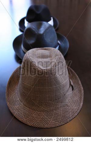Three Stylish Hats On Tabke