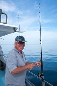 Happy mature smiling tourist on fishing boat charter with rod in Doubtless Bay, Far North District, New Zealand, NZ poster