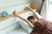 Young woman stretch arms in the air with alarm clock. wake up early in morning. Girl stop snooze alarm. female waking up sleepy and tired. woman wake up in the morning with alarm clock snooze. poster