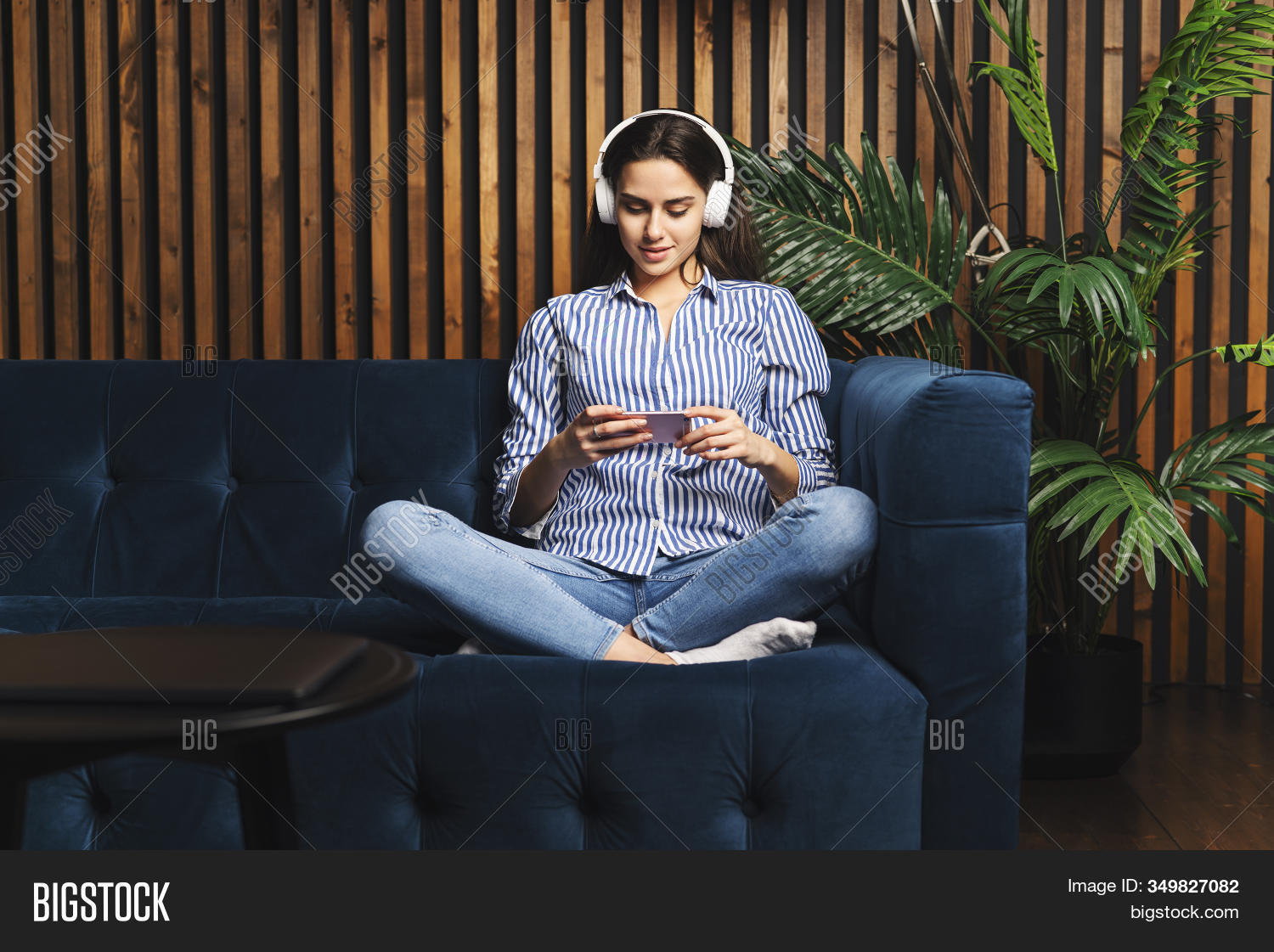 Pretty Millennial Woman Wearing Headphones Texting On Smartphone To Friend Online. Young Woman Strea