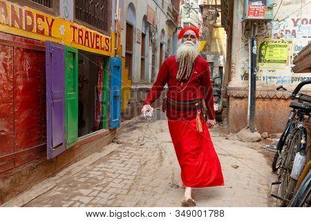 VARANASI, INDIA, JANUARY 20, 2019 : A smart looking colorful baba man is walking proudly in a street of Varanasi.