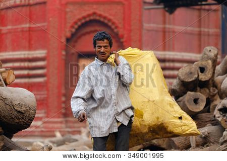 VARANASI, INDIA, JANUARY 19, 2019 : A man is carrying a full bag of tree logs for a traditional cremation ceremony along the Ganga river.