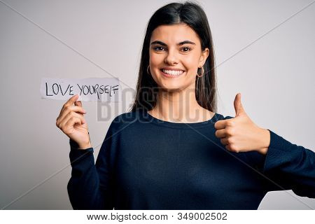Young beautiful woman asking for take care of you holding paper with love yourself message happy with big smile doing ok sign, thumb up with fingers, excellent sign