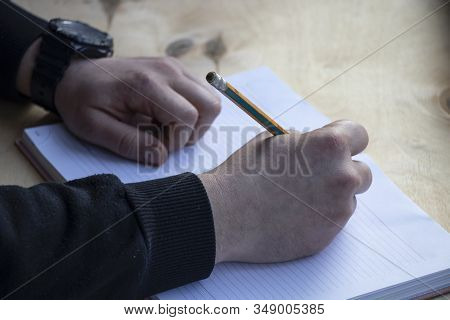 I Fill Out A Diary, A Desktop With A Notebook And Pen, Glasses And A Pencil On A Wooden Background.