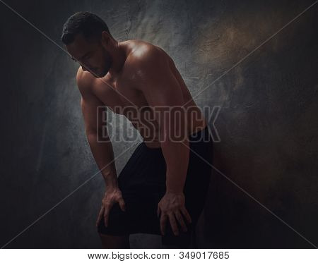 In The Dark Room Tired Shirtless Man Is Leaning To The Wall.