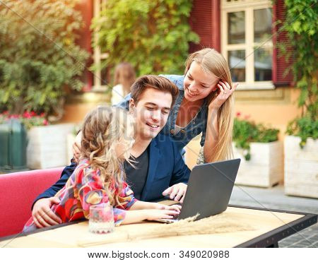 Young Family Together With Their Daughter Have Fun Looking At A Laptop In The Summer On The Street