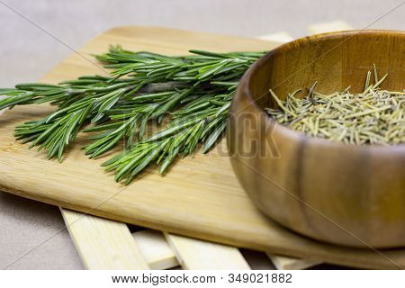 Bright Fresh Green And Dried Rosemary Branches, Twigs And Leaves In A Wooden Bowl And Board On Light