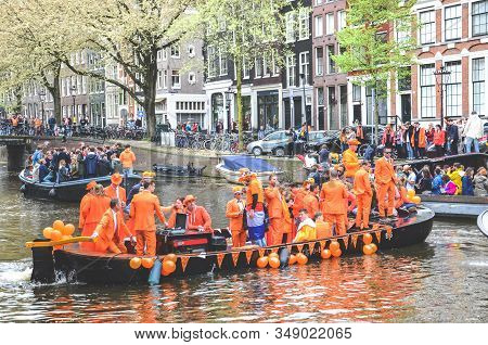 Amsterdam, Netherlands - April 27, 2019: People On Party Boats Dressed In National Orange Color Whil