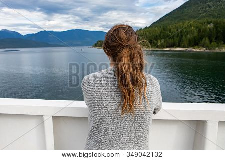 Close Up Shot From Behind Of A Female Passenger Of A Ferryboat Navigating In A Canadian Lake. Passen