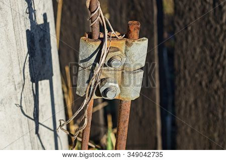 Lightning Conductor With Grounding From Gray Iron Plates On Nuts And Bolts On Steel Rusty Rods With