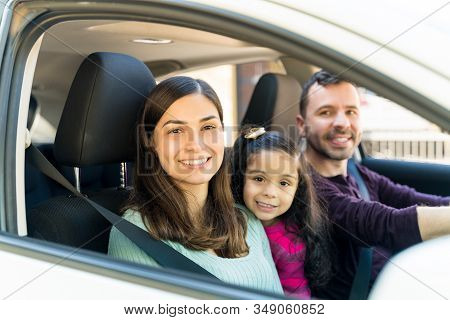 Happy Hispanic Family Sitting In Car During Weekend