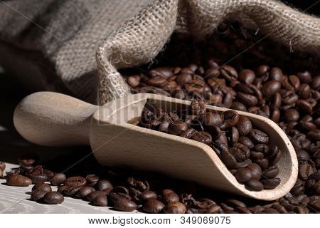 Coffee Beans In A Scoop With Hessian Bag On Wood