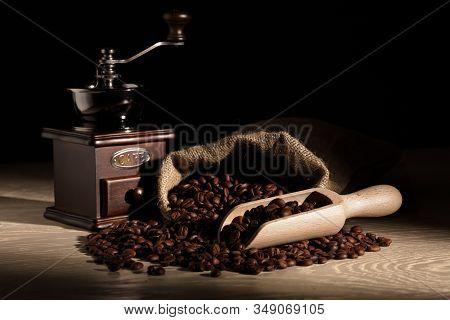 Coffee Beans With A Scoop Grinder And Hessian Sack On Wooden Surface