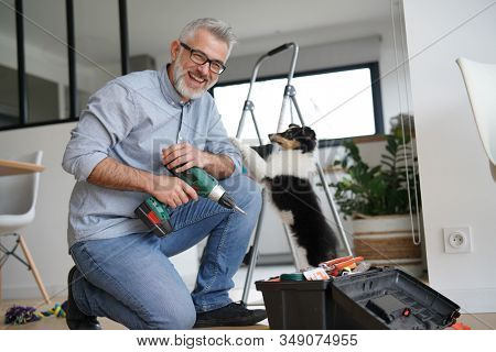 Man at home doing do-it-yourself work with puppy around