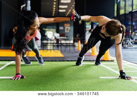 Healthy Women Giving High Five To Each Other While Pushing Up In The Fitness Gym. Sporty Girl Friend