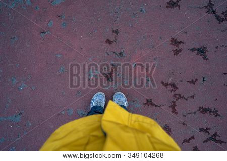Looking Down Photo Of A Woman Wearing A Yellow Rain Slicker And Her Shoes, On Red Pavement. Rainy Da