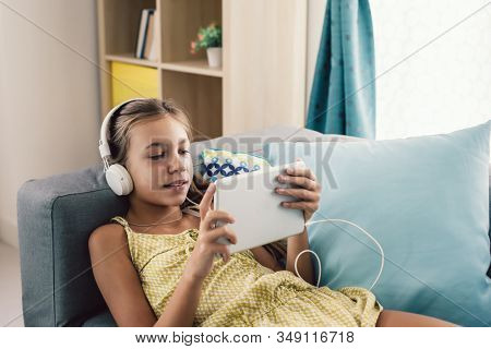 Pre teen child playing tablet and listening to music in head phones while relaxing on couch in living room at home.