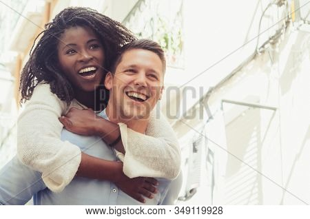 Young Man Laughing And Carrying Girlfriend On Back Outdoors. Happy Interracial Couple In Street. Rom